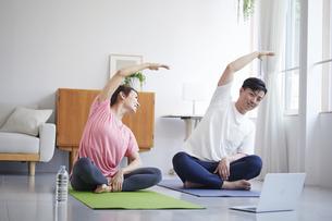 ノートパソコンを見ながら自宅でトレーニングをする若い男性と女性の写真素材 [FYI04922334]