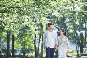 緑の中を歩く若い男性と女性の写真素材 [FYI04922344]