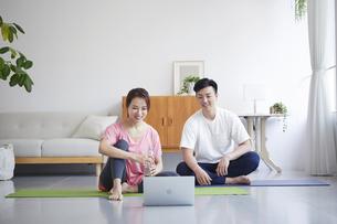 ノートパソコンを見ながら自宅でトレーニングをする若い男性と女性の写真素材 [FYI04922345]