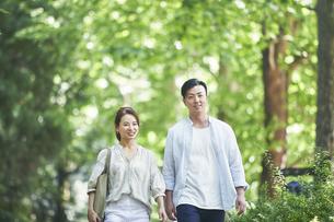 緑の中を歩く若い男性と女性の写真素材 [FYI04922347]