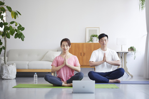 ノートパソコンを見ながら自宅でトレーニングをする若い男性と女性の写真素材 [FYI04922349]