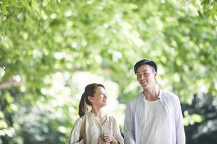 緑の中を歩く若い男性と女性の写真素材 [FYI04922353]