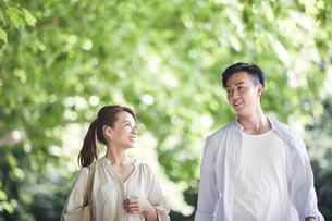 緑の中を歩く若い男性と女性の写真素材 [FYI04922360]