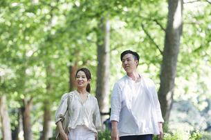 緑の中を歩く若い男性と女性の写真素材 [FYI04922364]