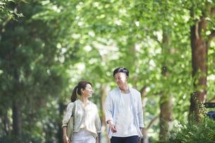 緑の中を歩く若い男性と女性の写真素材 [FYI04922368]