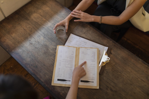 カフェのメニューと2人の女性の手の写真素材 [FYI04923623]