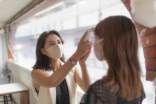 検温するマスク姿の2人の女性の写真素材 [FYI04923634]