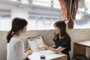 カフェでメニューを見る2人の女性の写真素材 [FYI04923915]