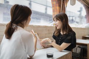 カフェでメニューを見る2人の女性の写真素材 [FYI04923916]