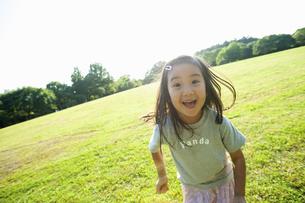 公園で楽しそうな表情をする女の子の写真素材 [FYI04924177]