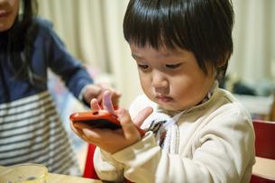 スマートフォンを操作する幼児の写真素材 [FYI04924213]
