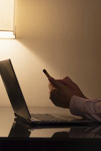 デスクに置かれたノートパソコンとスマートフォンを操作する手の写真素材 [FYI04924267]