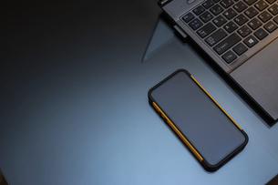 デスクに置かれたノートパソコンとスマートフォンの写真素材 [FYI04924271]