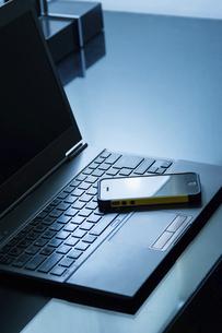 デスクに置かれたノートパソコンとスマートフォンの写真素材 [FYI04924272]