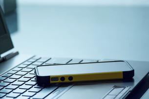 デスクに置かれたノートパソコンとスマートフォンの写真素材 [FYI04924273]