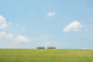 草原の2脚のベンチと青空の写真素材 [FYI04924293]