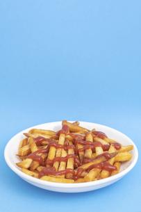 【料理】ケチャップをかけたフライドポテト 青背景の写真素材 [FYI04924796]