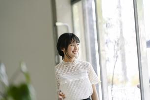 窓の外を眺める若い日本人女性の写真素材 [FYI04926930]