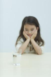 水の入ったコップを見つめる子供の写真素材 [FYI04927040]