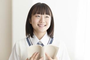 本を抱える女子高生の写真素材 [FYI04929101]