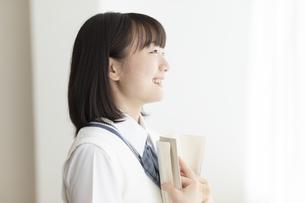 本を抱える女子高生の写真素材 [FYI04929102]