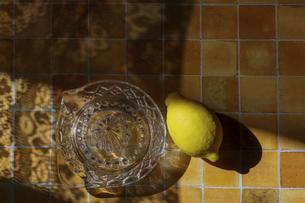 タイルパターン背景のレモンとガラスのレモン絞り器の写真素材 [FYI04929459]
