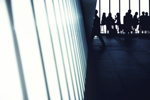 オフィスビルと人物シルエットの抽象的なイメージの写真素材 [FYI04929831]