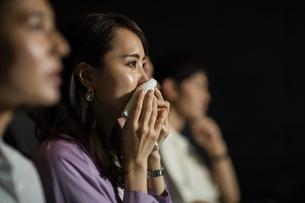 映画を観て涙をハンカチで拭う女性の写真素材 [FYI04930364]