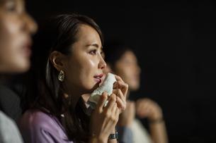 映画を観て涙する女性の写真素材 [FYI04930365]