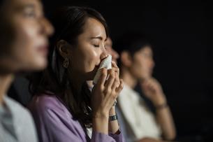 映画を観て涙をハンカチで拭う女性の写真素材 [FYI04930369]