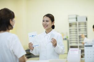 薬の説明をする女性薬剤師と患者の写真素材 [FYI04930387]