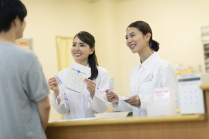 薬の説明をする2人の女性薬剤師と患者の写真素材 [FYI04930388]