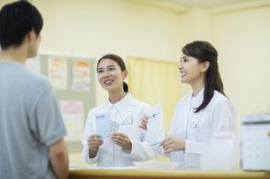 薬の説明をする2人の女性薬剤師と患者の写真素材 [FYI04930389]