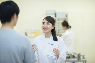 薬の説明をする女性薬剤師と患者の写真素材 [FYI04930390]