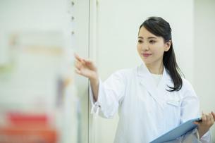 棚から薬をとる女性薬剤師の写真素材 [FYI04930391]