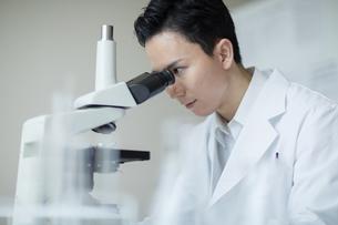 顕微鏡を覗く男性研究員の写真素材 [FYI04930392]