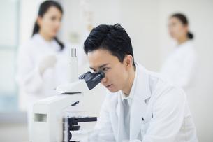 顕微鏡を覗く男性研究員の写真素材 [FYI04930394]