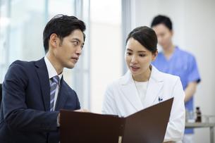 打ち合わせをするビジネスマンと女医の写真素材 [FYI04930426]