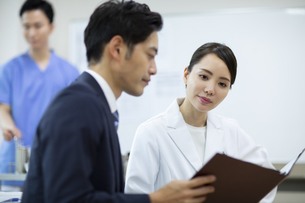 打ち合わせをするビジネスマンと女医の写真素材 [FYI04930427]