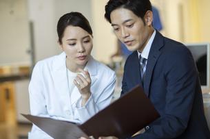 打ち合わせをするビジネスマンと女医の写真素材 [FYI04930428]