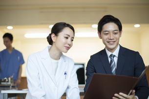 打ち合わせをするビジネスマンと女医の写真素材 [FYI04930429]