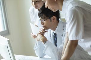 モニターを見て打ち合わせをする医師と看護師たちの写真素材 [FYI04930472]
