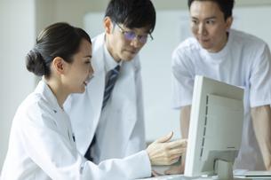 モニターを見て打ち合わせをする医師と看護師たちの写真素材 [FYI04930476]