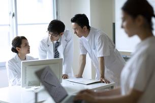 モニターを見て打ち合わせをする医師と看護師たちの写真素材 [FYI04930480]