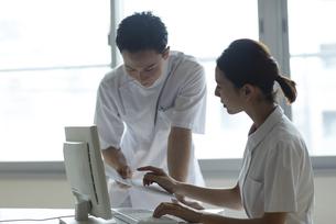 モニターを見て打ち合わせをする医師と看護師たちの写真素材 [FYI04930487]