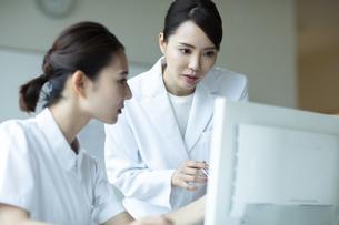 モニターを見て打ち合わせをする医師と看護師たちの写真素材 [FYI04930488]