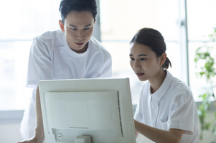 モニターを見て打ち合わせをする医師と看護師たちの写真素材 [FYI04930492]