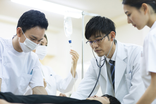 救急患者の診察を行う医師と看護師の写真素材 [FYI04930496]