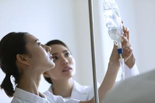 点滴の確認を行う女医と女性看護師の写真素材 [FYI04930510]