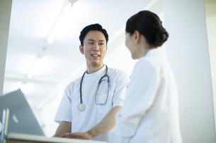 PCの前で打ち合わせをする男性看護師と女医の写真素材 [FYI04930520]